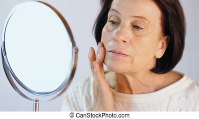 Elderly woman looking at skin on the face
