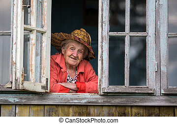 Elderly woman looking from the window of the farmhouse.