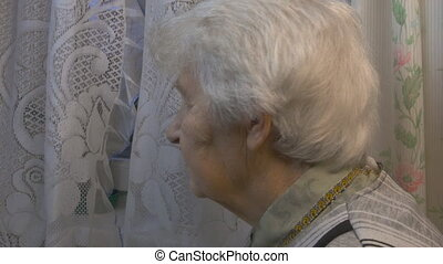 Elderly woman looking to window
