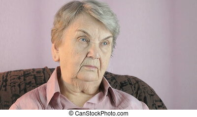Elderly woman looks in the direction indoors - Elderly woman...