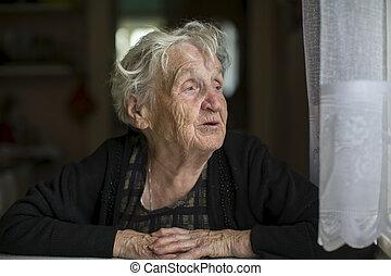 Elderly woman looks out the window.