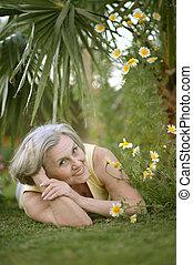 Elderly woman lying at resort