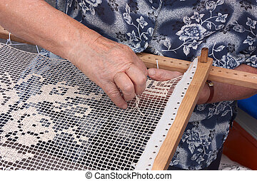 elderly woman making an embroidery with the wooden frame - handmade traditional needlework