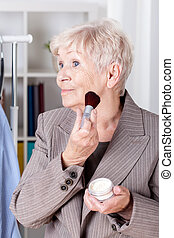 Elderly woman making up