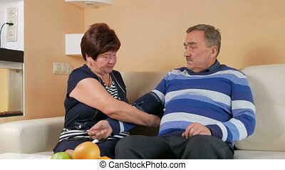 Elderly woman measures the blood pressure at home on the couch. Poor man's well-being. Taking care of his wife about her husband