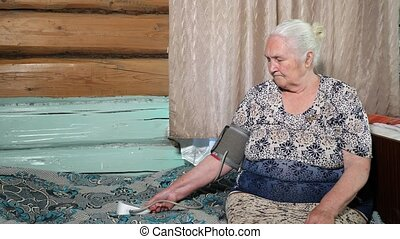 elderly woman measures the pressure with a blood pressure monitor, sitting on the bed.
