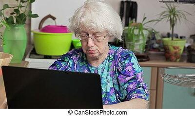 Elderly woman near laptop