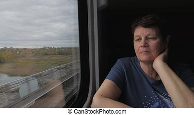 Elderly woman near window in train