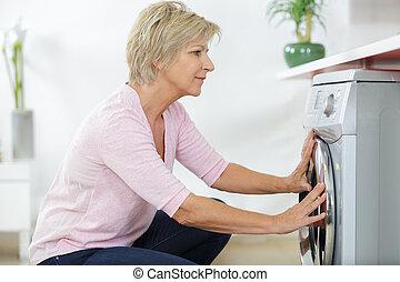 elderly woman next to a washing machine