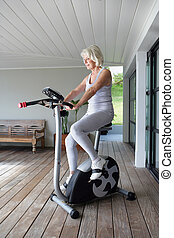 Elderly woman on an exercise machine