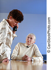 Elderly woman on appointment with social worker. Shallow DOF, focus on elderly lady.