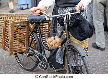 elderly woman on bike with two fresh eggs in hand