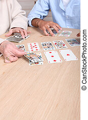 Elderly woman playing card game with young man
