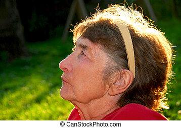 Elderly woman - Portrait of an elderly woman outside with...