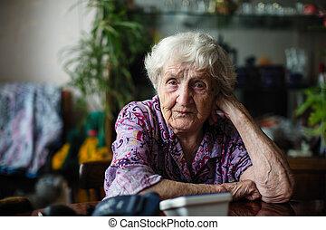 Elderly woman portrait sitting in a room.