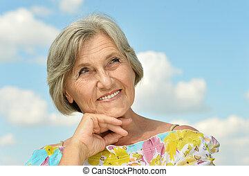 elderly woman posing against the sky