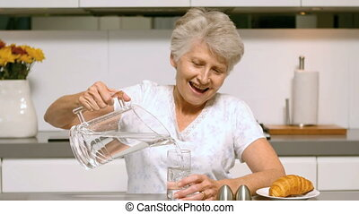 Elderly woman pouring a glass of wa