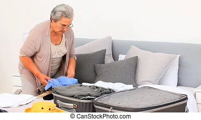Elderly woman preparing her luggage
