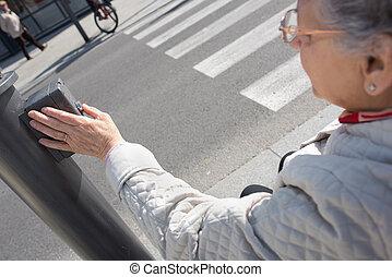 elderly woman pressing crosswalk button