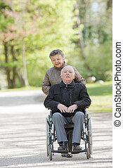 elderly woman pushing man in wheelchair