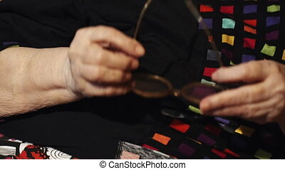 Elderly woman putting on glasses