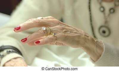 Elderly woman putting on golden rings. Senior woman hands...