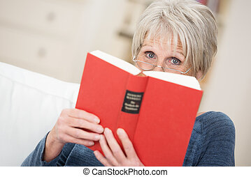 Elderly woman reading a book at home