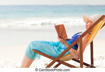Elderly woman reading a book at the