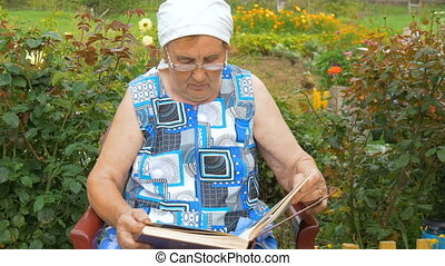 Elderly woman reading a book while sitting in his garden.