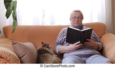 Elderly woman reading a book while sitting on sofa