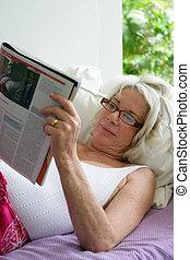 Elderly woman reading a magazine