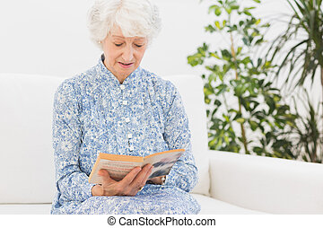 Elderly woman reading a old book