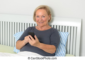 Elderly woman reading an sms on her mobile phone
