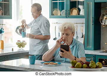 Elderly woman reading bad news on a cell phone