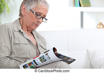 Elderly woman reading magazine