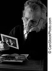 elderly woman reading old letters and looking at old photographs