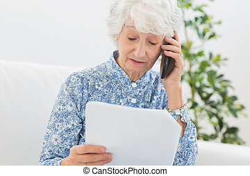 Elderly woman reading papers on the phone