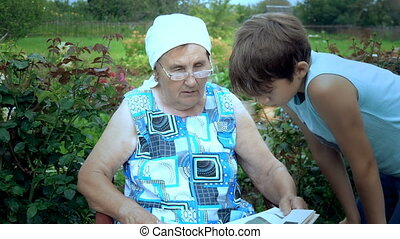 Elderly woman reads the book to her grandson.