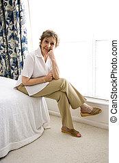 Elderly woman relaxing in her bedroom