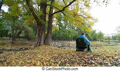 elderly woman resting at autumn