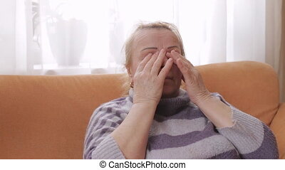Elderly woman rubs her eyes while sitting on the sofa