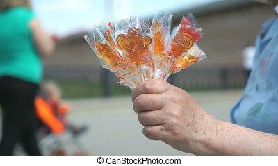 Elderly woman selling homemade lollipops - Elderly woman...