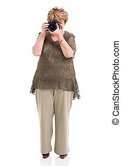 elderly woman shooting pictures with digital SLR camera on...