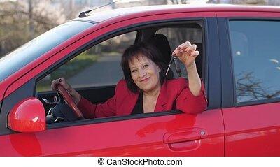 Elderly woman showing keys sitting in a car - Woman in new ...