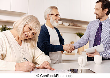 Elderly woman signing contract while her husband greeting the lawyer