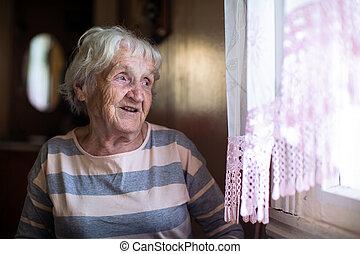 Elderly woman sits near the window.