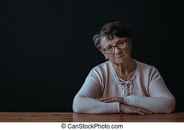 Elderly woman sitting alone