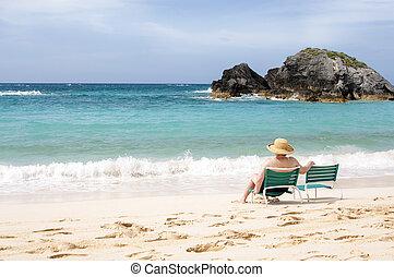 Elderly woman sitting and enjoying on sea beach