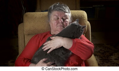 Elderly woman sitting in an armchair stroking her cat
