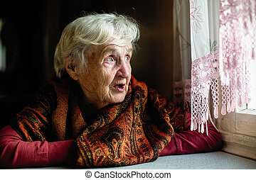 Elderly woman sitting in the house looks longingly out the window.